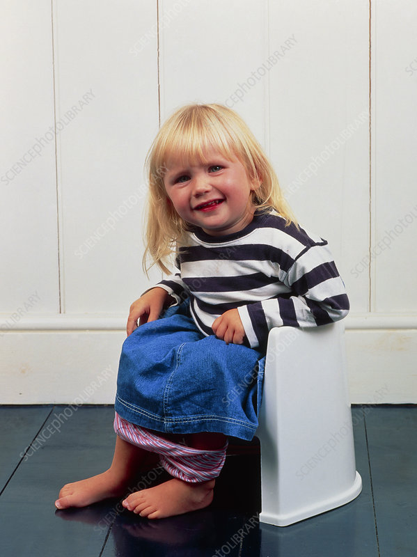 A constipated young girl using a potty