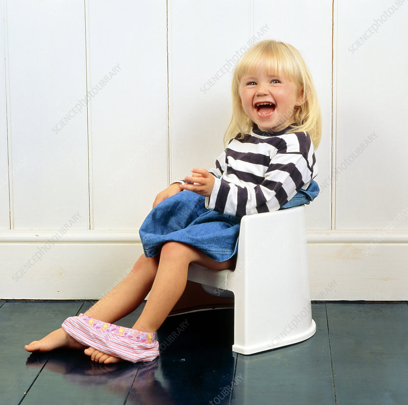 A laughing young girl using a potty