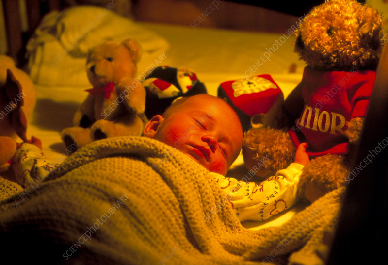 Young baby asleep in bed surrounded by toys