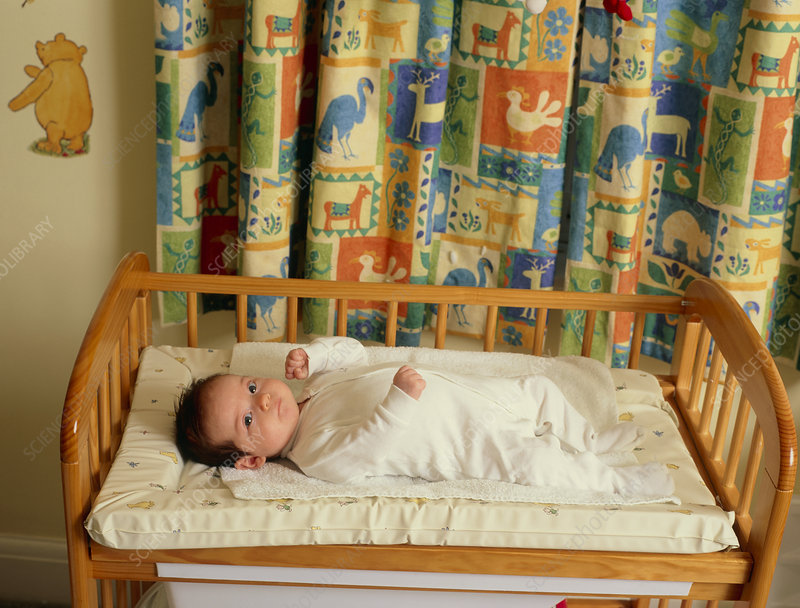 Baby lying on its back awake in a cot