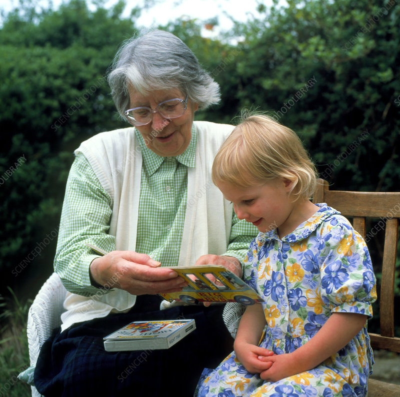 Grandmother reads to her young granddaughter
