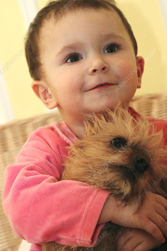 Infant holding a dog