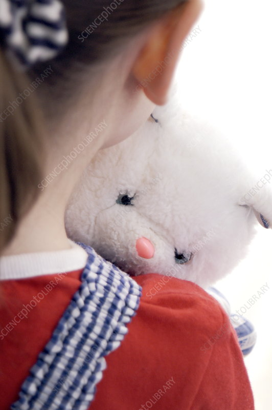 Young girl holding a cuddly toy