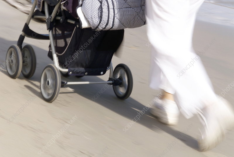 Mother pushing her baby in a pushchair