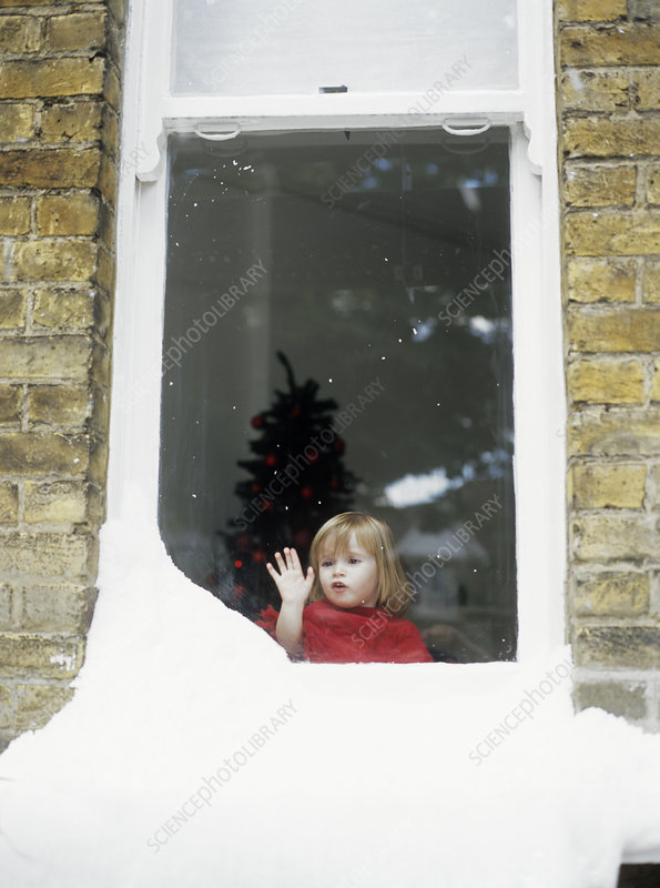 Girl staring out of snowy window