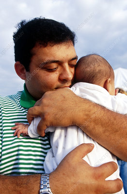 Hispanic man holds baby
