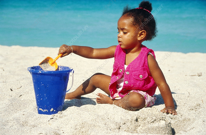 Toddler Pouring Sand into a Bucket