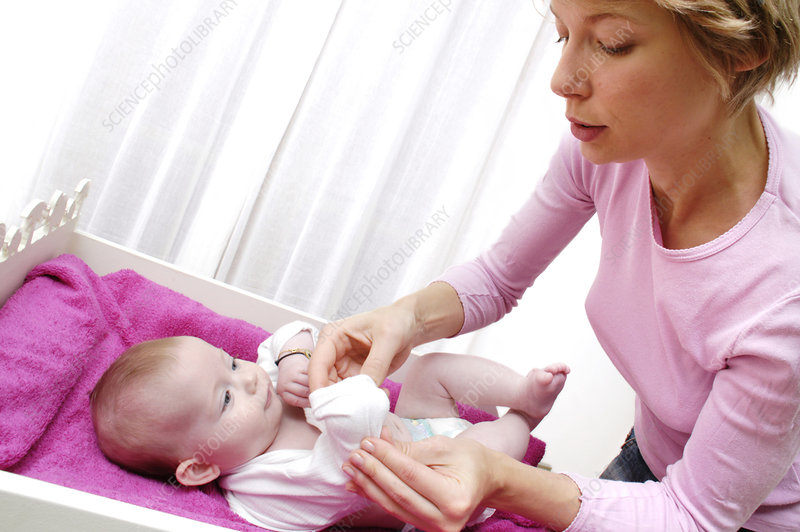 Mother dressing her baby