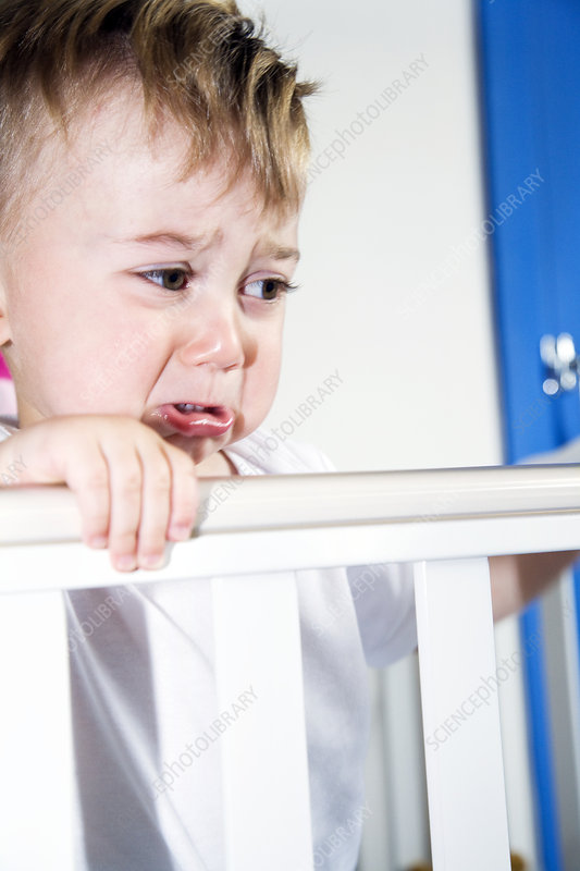Upset toddler in his cot