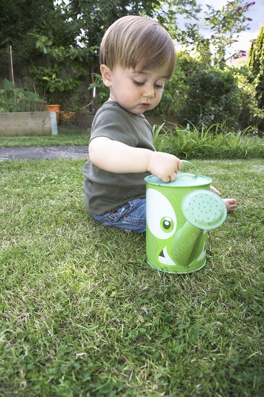 Toddler playing with a watering can