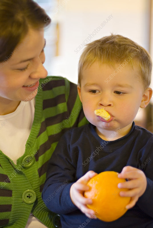 Toddler eating an orange