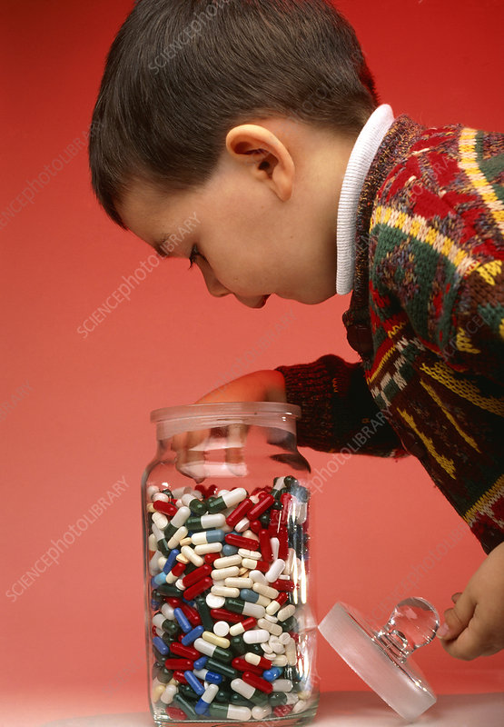 Boy taking pills and drug capsules from a jar