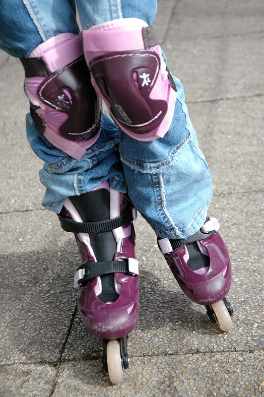 Child wearing rollerblades and knee pads
