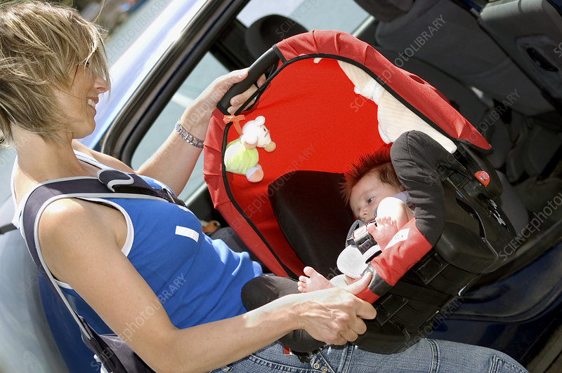 Mother with child in car seat