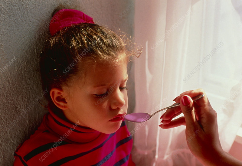 Sick young girl is fed a spoon of medicine