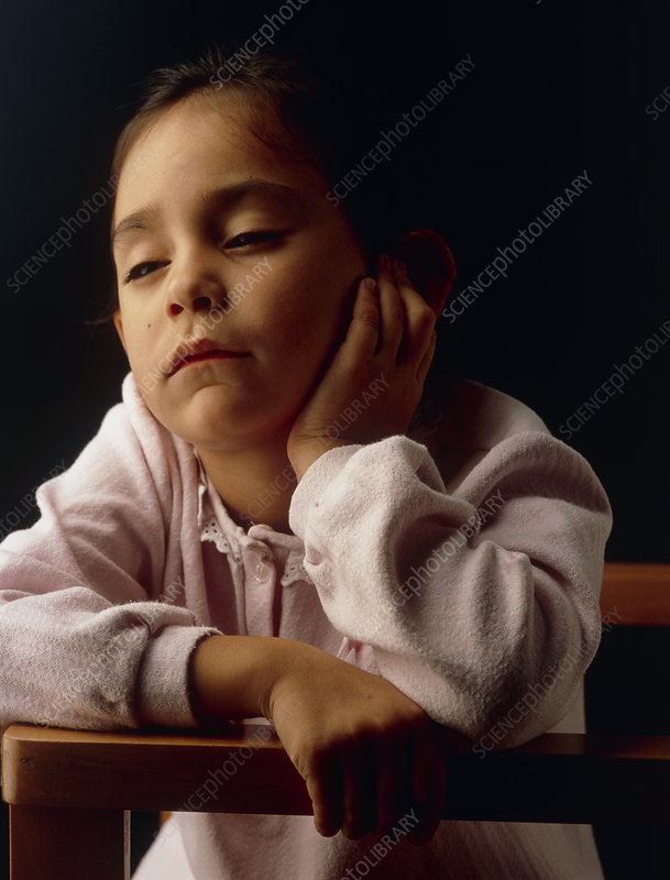 Unwell little girl rests her head in her hand