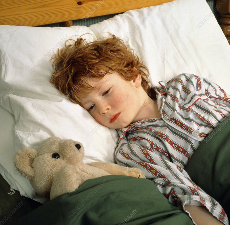 Feverish child in bed with teddy bear