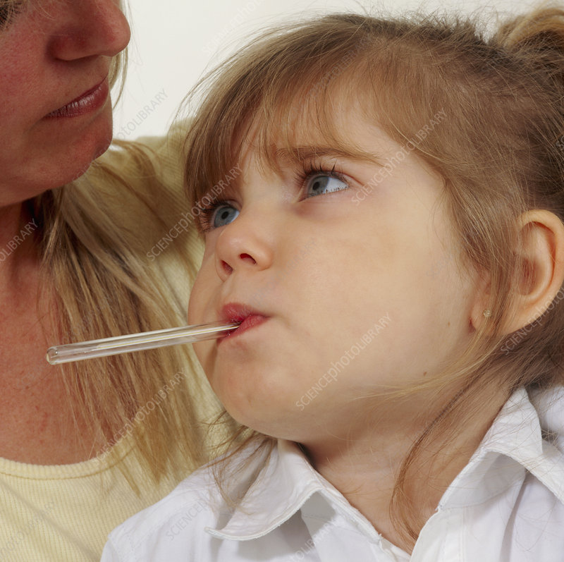 Young girl with fever has oral temperature taken