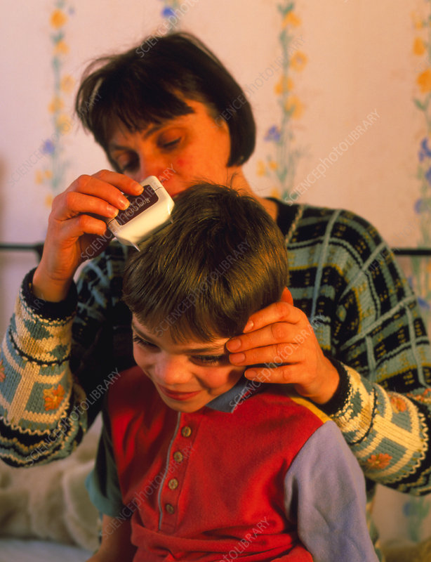Woman using an electronic nit comb on a boy's head