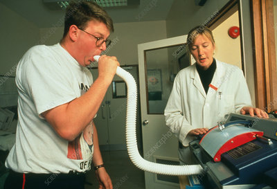 Asthmatic man breathes into a spirometer