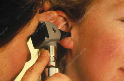 Otoscope ear examination of a woman