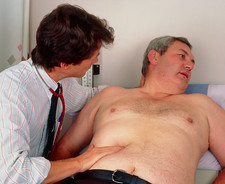 GP doctor examining man's abdomen for appendicitis