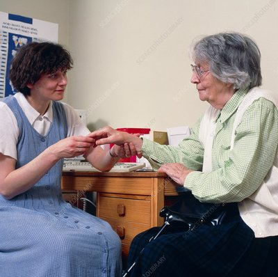 GP doctor examines an old woman's arthritic hand