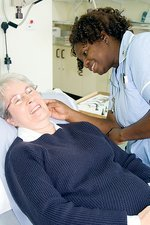 Nurse cleaning a patient's ear