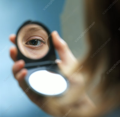 Woman examining her eye in a mirror