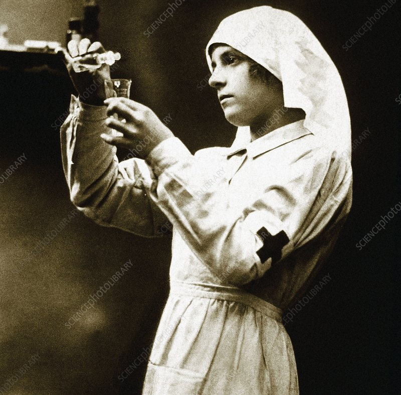 Woman hospital nurse pouring medicine, dated 1900