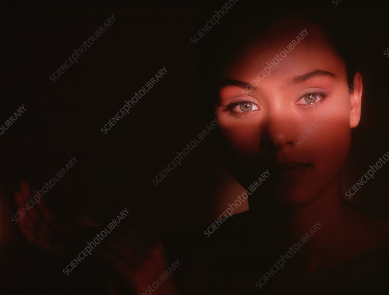 Woman in shadow with eyes lit