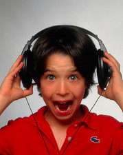 Young boy hearing a loud sound through headphones