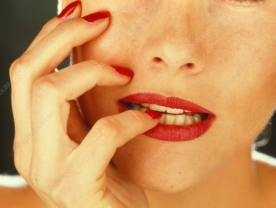 Woman's mouth biting her nail-varnished nails