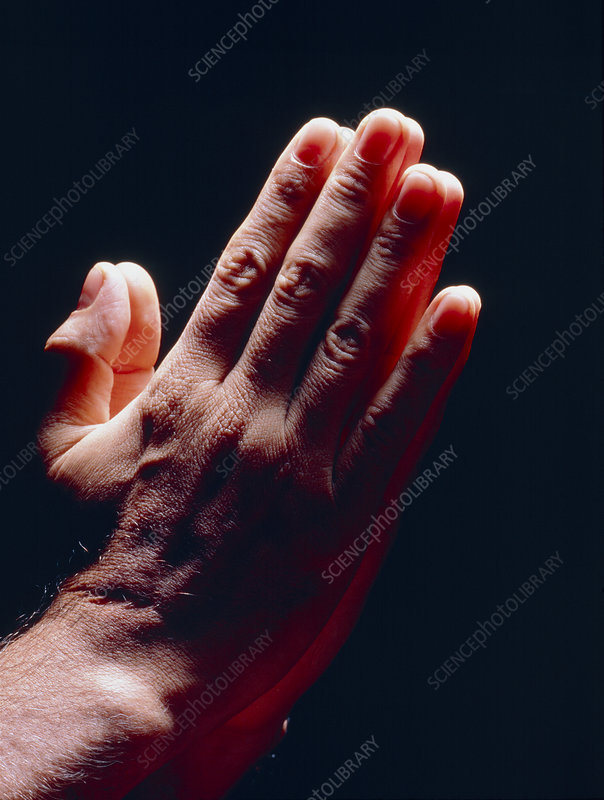 Side view of man's hands held together in prayer