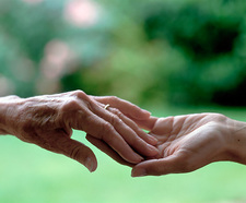 View of an elderly hand touching a younger hand