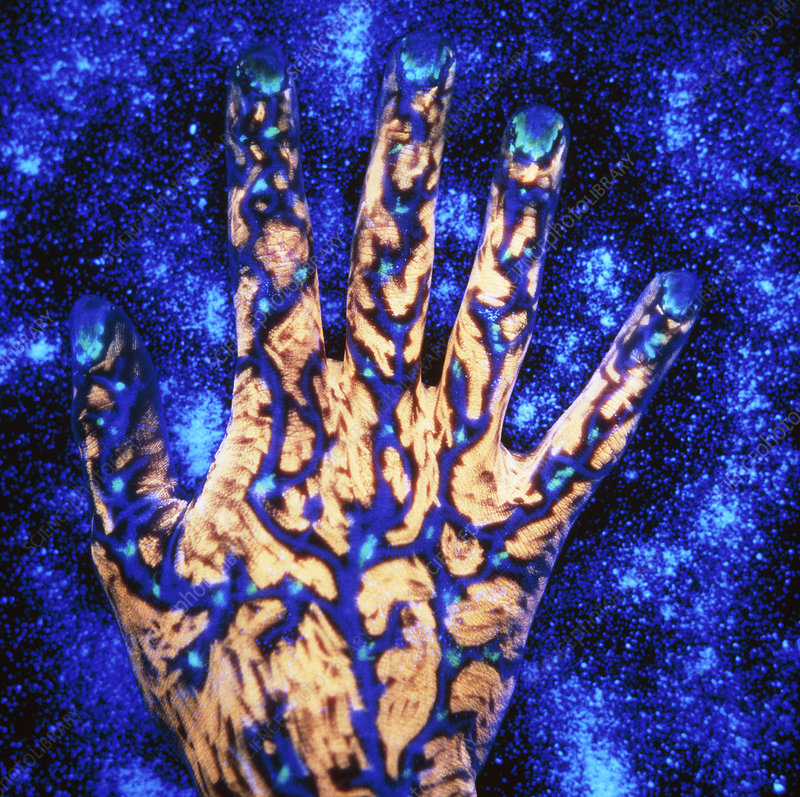 Fluorescent ink on hand, starry blue background