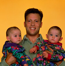 Infant identical twins being held by proud father