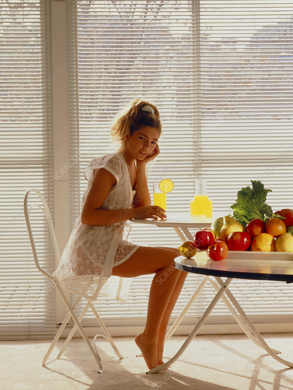 Woman drinking fruit juice beside a table of fruit