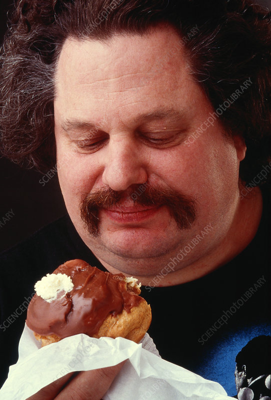 Obese man eating a cream and chocolate pastry