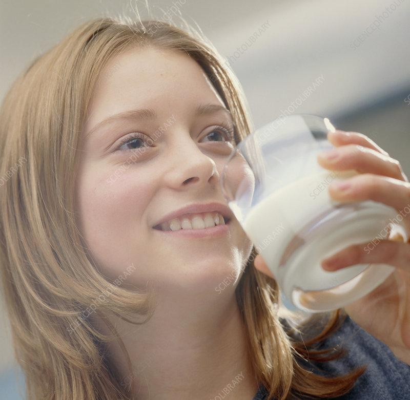 Teenage girl drinking a glass of milk