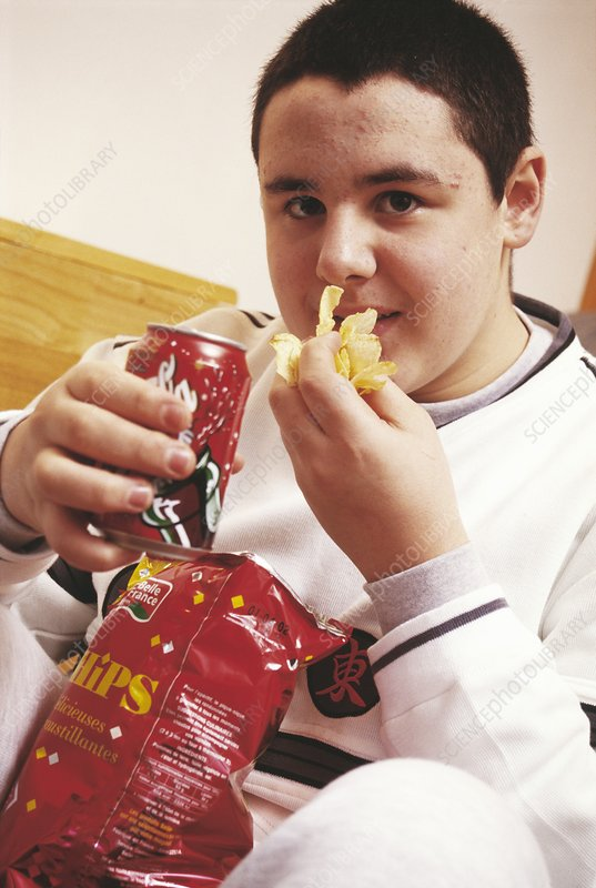 Junk food. Teenage boy eating crisps and drinking cola, both of which can be