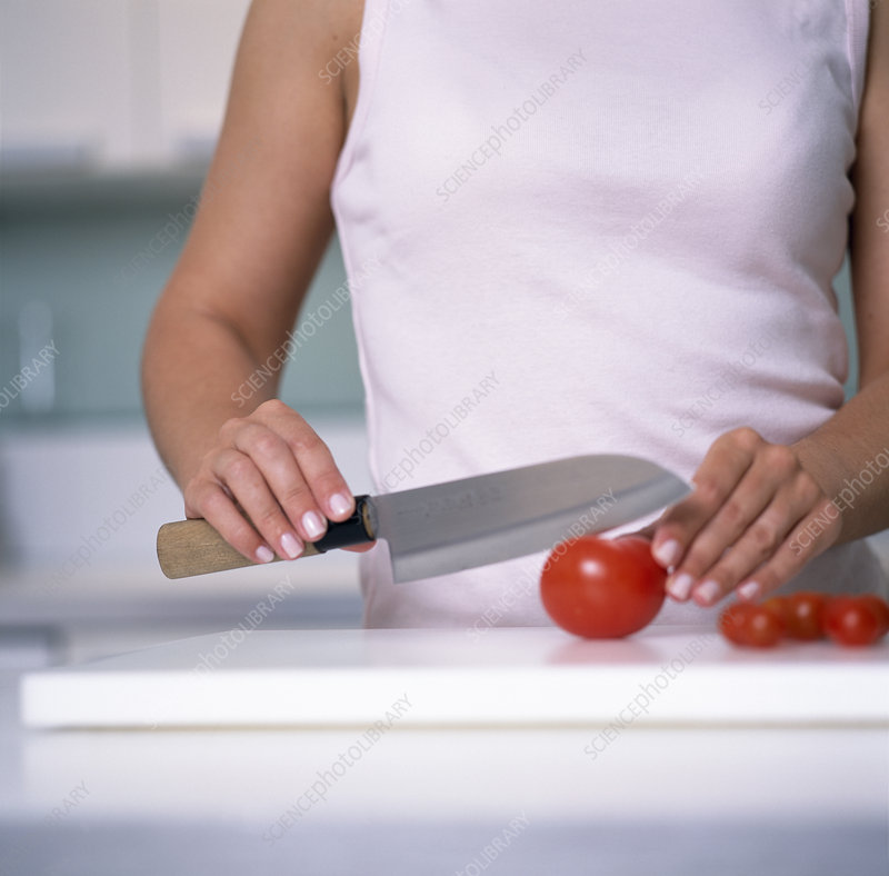 Woman cutting a tomato
