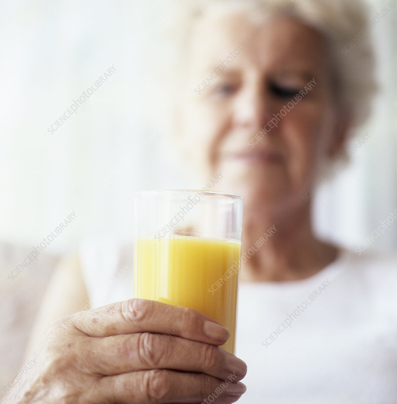 Elderly woman holding glass of juice