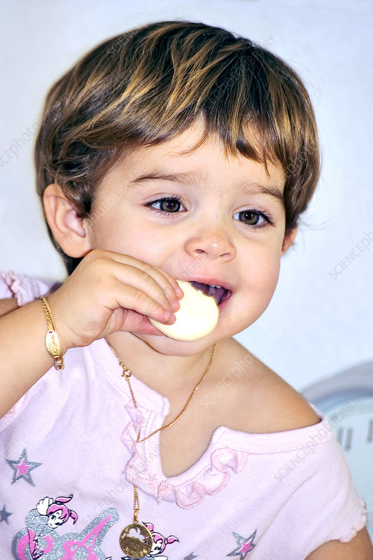 Young boy eating a sweet