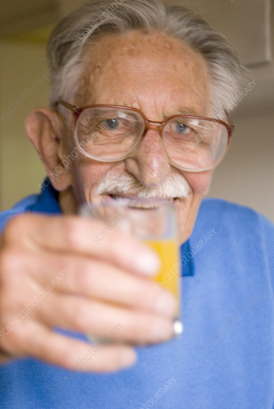 Elderly man holding a glass of juice