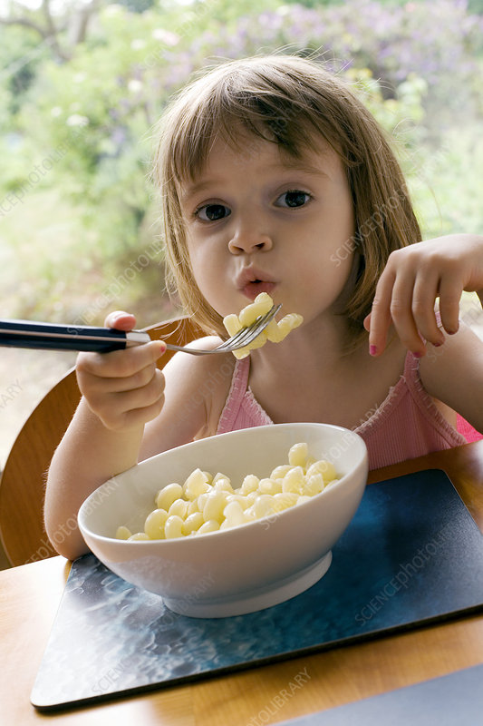 Young girl eating pasta