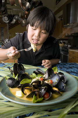 Boy eating mussels