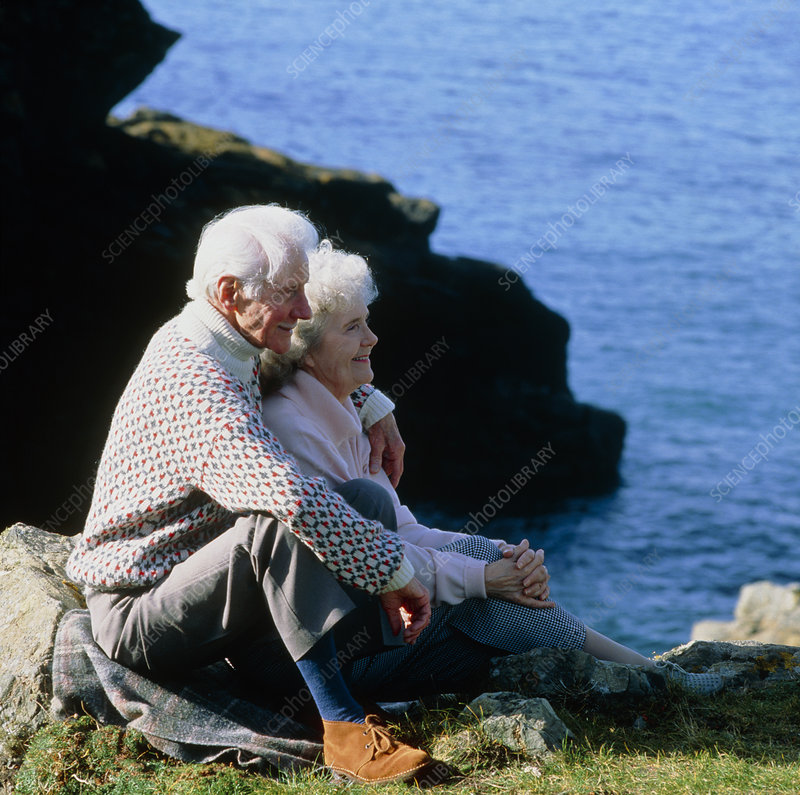Elderly couple sit at the top of a rocky coast