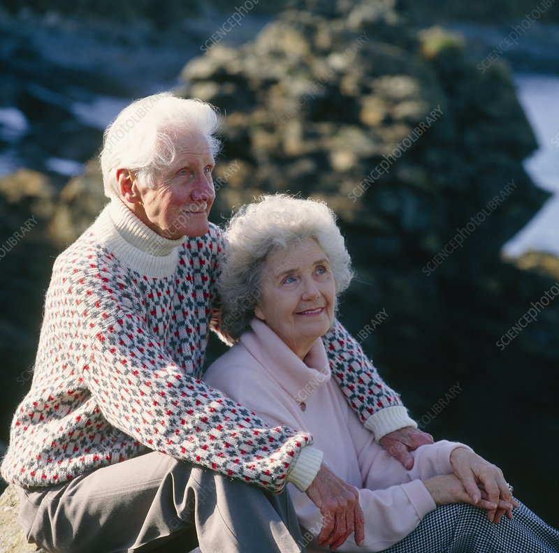 Elderly couple sit together at a rocky coast
