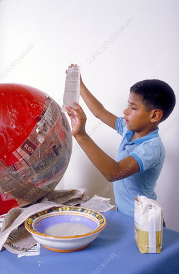 Hispanic boy working on tomato pinata